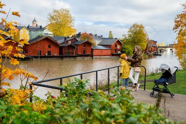 ポルヴォー、フィンランド、川の堤防上の母と息子。古い赤い家の納屋の背景に