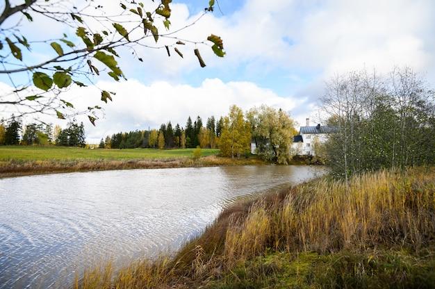 野原の間の川、海岸のホワイトハウス。美しい秋の風景。ヘルシンキ、フィンランド