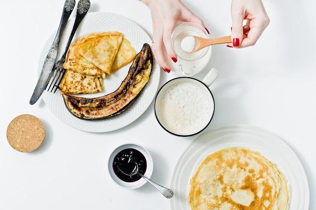 少女は一杯の砂糖を一杯のコーヒーに入れ、朝食はパンケーキで朝食をとる。
