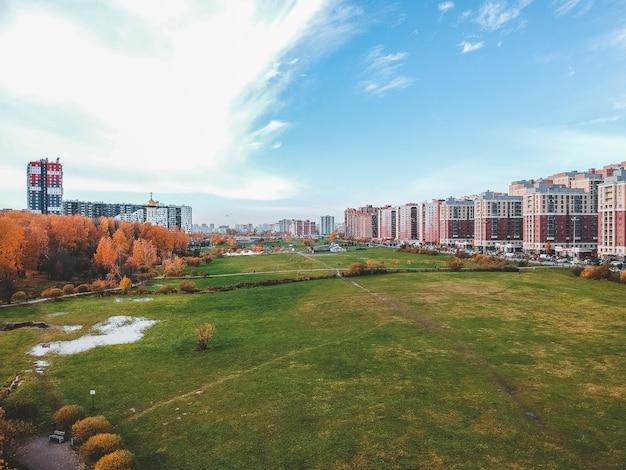 Вид с воздуха на окрестности, прекрасный осенний парк и многоэтажное жилое строительство. санкт-петербург, россия
