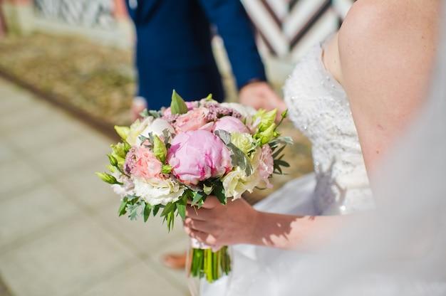 Невеста держит свадебный букет из роз и пионов.