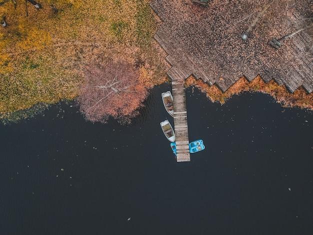 湖の岸に木製のボートと空撮桟橋