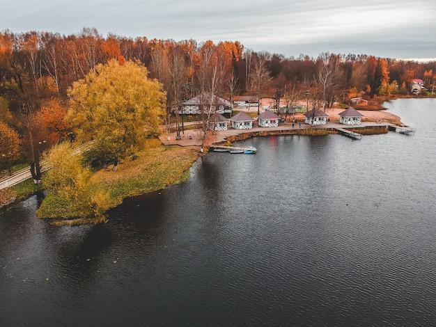Вид с воздуха на лес и голубое озеро. баня на берегу озера. деревянный пирс с рыбацкими лодками. санкт-петербург, россия.