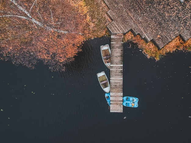 Пристань вида с воздуха с деревянными шлюпками на береге живописного озера, лесом осени. санкт-петербург, россия.