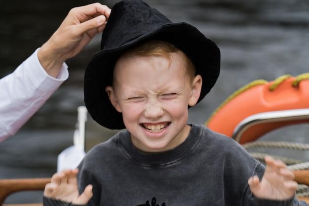 ヨットの上で笑顔の魅力的な赤毛の少年。
