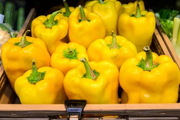 黄色のピーマン、木製の箱、市場。農場のエコ製品。