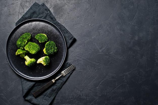 Брокколи на черной тарелке.