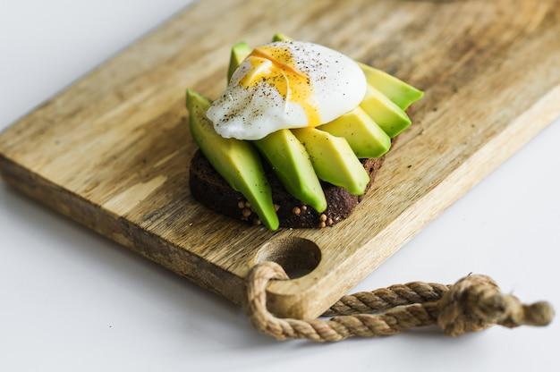 Тост, бутерброд с авокадо и яйцо-пашот на деревянной разделочной доске.
