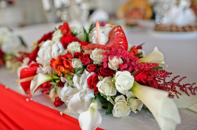 レストランでの結婚式のディナー、バラの花瓶で飾られたテーブル。