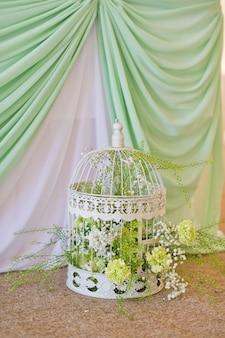 花、小さなバラ、菊で作られた花輪で飾られたビンテージ鳥かご