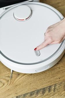 女の子の手がロボット掃除機をオンにします。