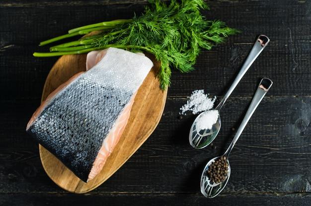 Атлантический сырой лосось, стейк и петрушка веточка на черном фоне деревянных