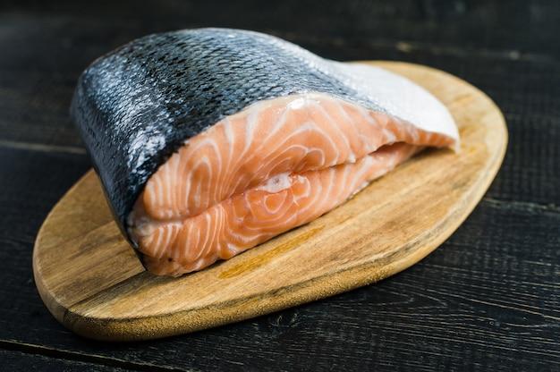 Атлантический сырой лосось, стейк на черном фоне деревянных