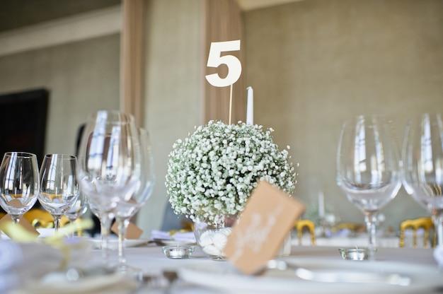 レストランの結婚式の宴会で設定されたテーブル、白いテーブルクロスとナプキンのクラシックなスタイル、花が付いた花瓶。