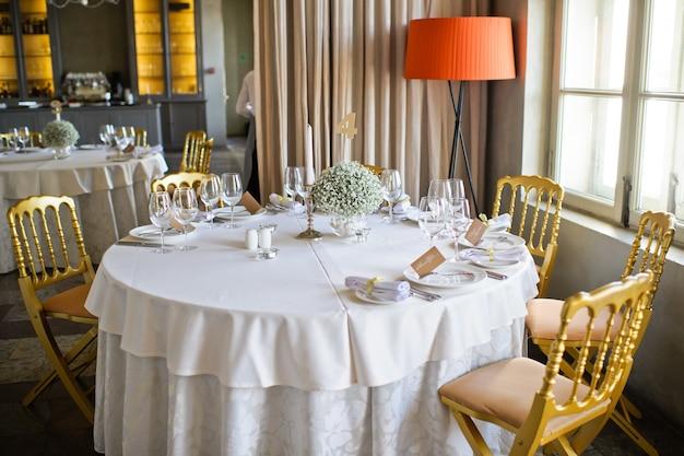 Столовый набор на свадьбу банкет в ресторане, классический стиль с белыми скатертями и салфетками, вазы с цветами.