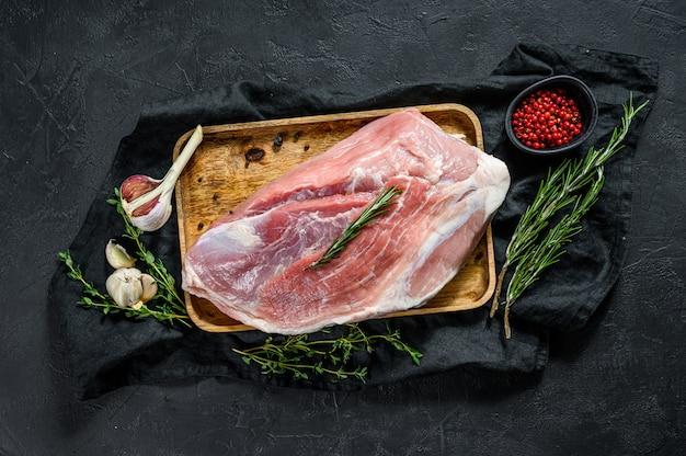 新鮮なポークカット。生肉とスパイス。後ろ脚のステーキ。黒の背景。上面図