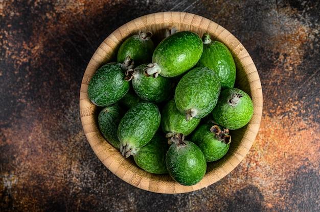 Зеленое фейхоа приносить в деревянной плите на темной предпосылке. тропический фрукт фейхоа. вид сверху