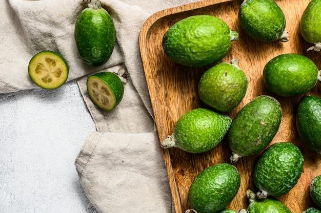 Зеленое фейхоа приносить в деревянной плите на серой предпосылке. тропический фрукт фейхоа. вид сверху