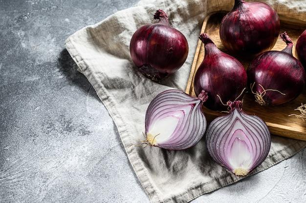 木製のボウルに赤玉ねぎ、玉ねぎ半分。ファームエコ野菜。灰色の背景。上面図