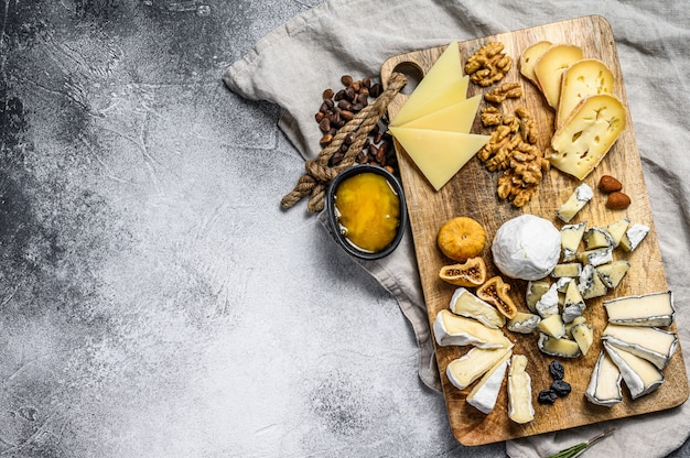 Сырное ассорти с французскими органическими сырами, инжир, орехи на сером фоне. вид сверху. вкусный сырный стартер