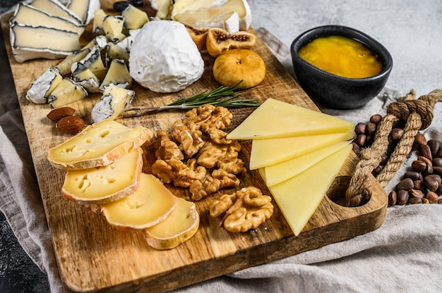 Ассорти из французских сыров с медом, орехами и инжиром на разделочной доске. серый фон вид сверху.