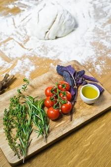 フォカッチャの材料:生地、トマト、ローズマリー、タイム、バジル、オリーブオイル、木製のテーブル。