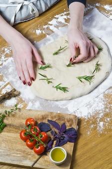 シェフはフォカッチャを準備し、生地にローズマリーを産みます。