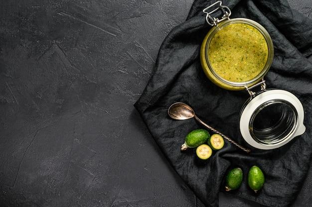 ガラスの瓶に木製のまな板に緑のフェイジョアジャム。