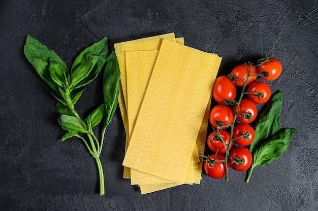 Сырые листы лазаньи. ингредиенты базилик, помидоры черри