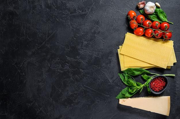 Сырые листы лазаньи. ингредиенты базилик, помидоры черри, пармезан, чеснок, перец