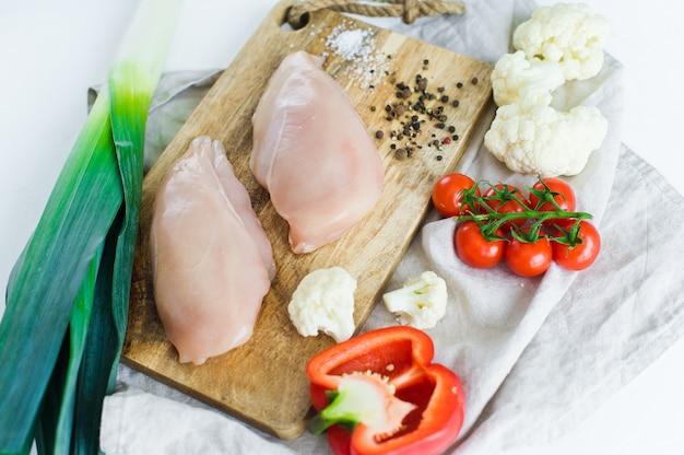 Сырые куриные грудки на деревянной разделочной доске.