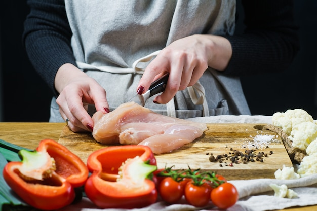 Шеф-повар режет куриные грудки на деревянной разделочной доске.