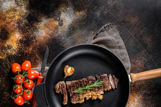 Стейк из говяжьей вырезки на сковороде.