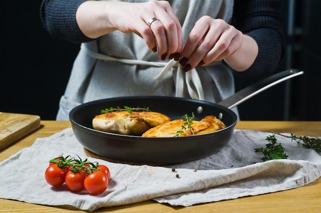 Шеф-повар посыпает тимьяном куриные грудки на сковороде.