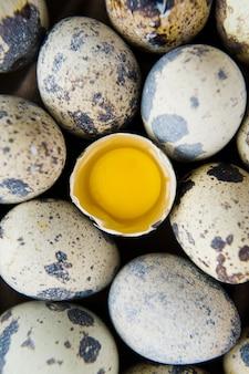 Перепелиные яйца, одно сломанное яйцо.