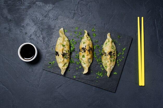 黒い石板、黄色い箸で揚げた韓国餃子。
