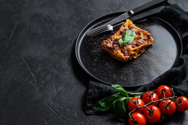 Кусочек вкусной горячей лазаньи. традиционная итальянская кухня. пространство для текста