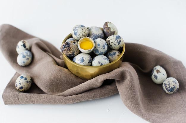 Перепелиные яйца в золотой миске, одно сломанное яйцо.