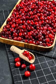 木製ボウル黒熟した表面で熟した赤いクランベリー