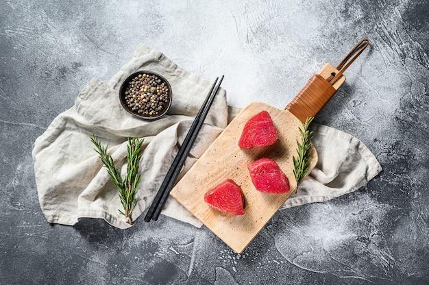 Сырой стейк из красного тунца. серый фон вид сверху. пространство для текста