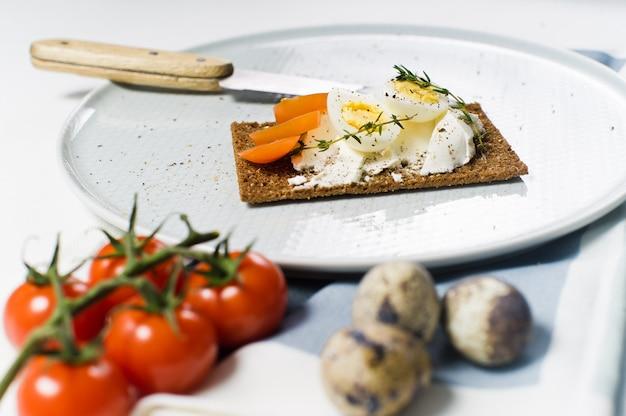ウズラの卵焼き。材料トマト、卵、チーズ、ライ麦パン。