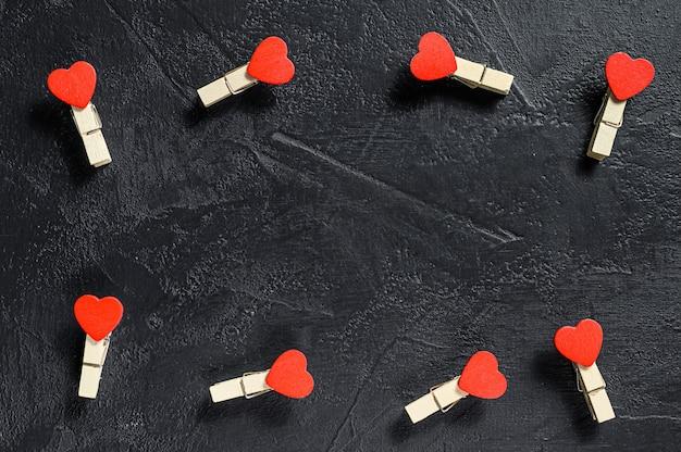 バレンタインデーのコンセプト。赤いハートと洗濯はさみ。黒の背景。上面図。コピースペース