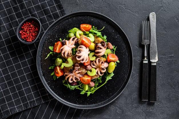 Домашний салат с осьминогом и картофелем, рукколой, помидорами и оливками.