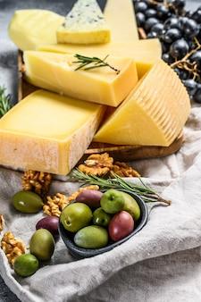 Сырная тарелка подается с виноградом, крекерами, оливками и орехами. ассорти вкусных закусок. вид сверху