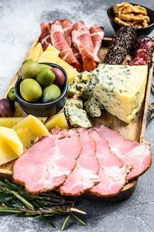 Антипасто различные закуски, разделочная доска с прошутто, салями, коппа, сыр и оливки. вид сверху