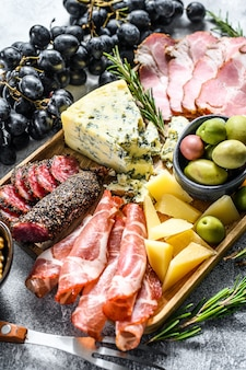 Итальянские закуски или антипасто устанавливают смешанными деликатесами из сыра и мясных закусок. вид сверху