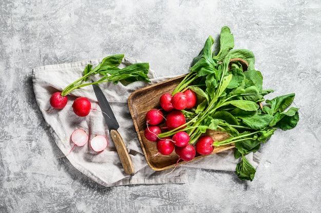 Свежие красные редиски в деревянной миске. ферма органических овощей. вид сверху