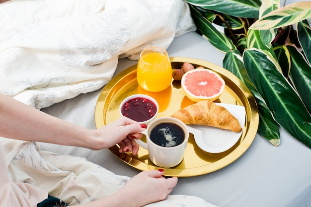ベッドで朝食のクロワッサンを食べる女子高生。