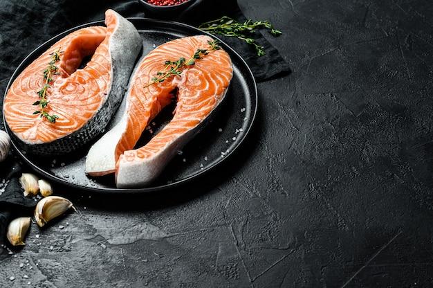 スパイスプレートに生のサーモンステーキ。大西洋の魚。上面図。コピースペース