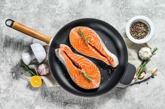 Сырой стейк из форели на сковороде. здоровые морепродукты. вид сверху.